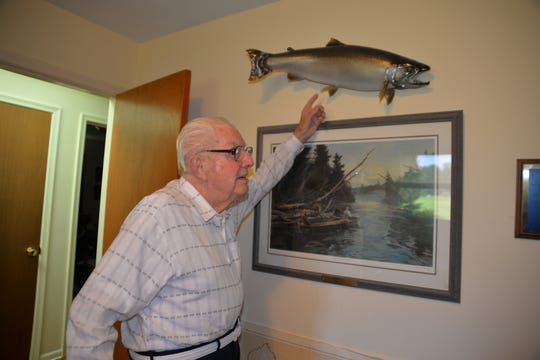 Acclaimed Michigan conservationist Howard Tanner shows off a mounted steelhead trout that hangs in his home office above a painting of kids fishing in the Au Sable River. Tanner got his start in fish conservation working as a fishing guide on the Au Sable in the 1930s.