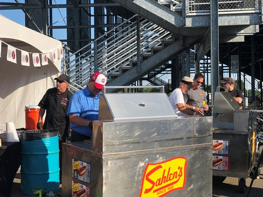 Watkins Glen International President Michael Printup, left, and Sahlen Packing Company owner/president Joe Sahlen serve hot dogs to fans during the Sahlen's Six Hours of The Glen weekend June 28, 2019 at WGI.