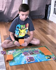 Johnny Piet, 7, of Big Flats, sets up his Pokemon trading card game board. Johnny will take part in a Pokemon national tournament Aug. 16 through 18.