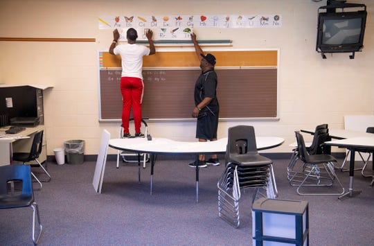 First-year teacher Watez E. Phelps II decorates his classroom at Lodge Elementary School with the help of his dad,  Watez Phelps Sr. in hopes of getting it ready for his students recently. Phelps will be teaching in the same room he spent his third-grade year in.in hopes of getting it ready for his students recently. Phelps will be teaching in the same room he spent his third-grade year in.