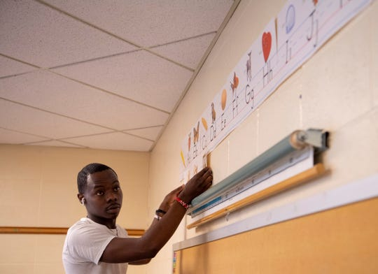First-year teacher Watez E. Phelps II decorates his classroom at Lodge Elementary School in hopes of getting it ready for his students recently. Phelps will be teaching in the same room he spent his third-grade year in.