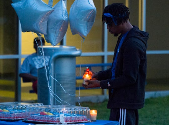 Lontae Pettie lights a candle to honor slain teen Jaiwaun Latrell Wadlington during a gathering of friends and family at Bellemeade Park for his birthday Wednesday, July 31, 2019. Wadlington was to turn 19 but was killed July 26 while attending a party at Thomason's Banquet Hall in Henderson, Kentucky.