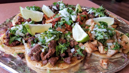 A platter of tacos with chorizo, tripa, lengua, pork al pastor, beef and chicken at Chicken 'n Salsa Mexican Restaurant.