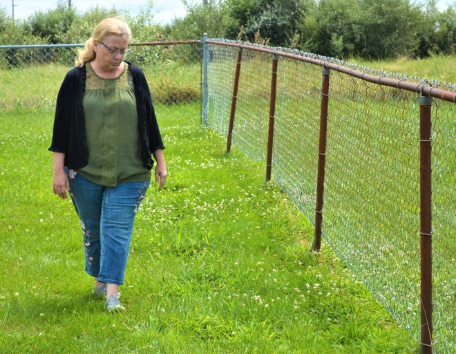 Janet Ramirez walks by a line of gravestones she and volunteers uncovered. She said the county inmate work crew does a great job mowing the cemetery, but the grass still tries to encroach upon the stones.