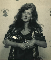 Bonnie Raitt holds four Grammys she won at the 1990 Grammy Awards in Los Angeles.