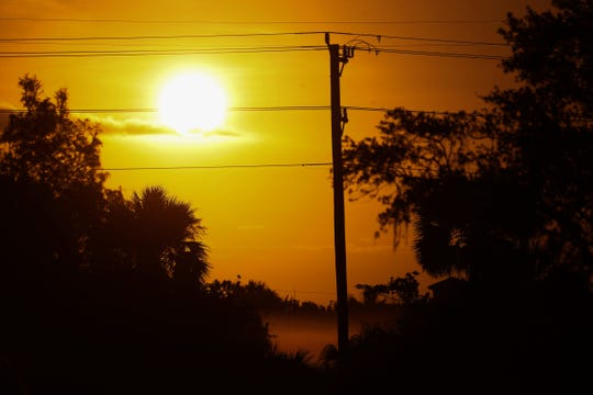 In this Sept. 12, 2017 photo, the sun rises over utility poles and North Fort Myers on Tuesday. Many in the area are still without power after Hurricane Irma raked the area.