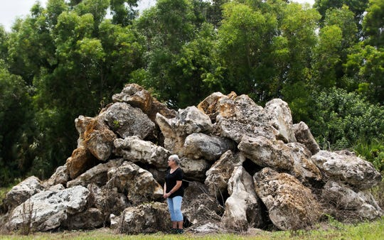"""Mary Ann Lehmann stands among boulders discarded near her home at the Lochmoor Country Club and Golf Course in North Fort Myers recently. Paradise Isle, a $600 million-$1 billion project to rejuvenate the foreclosed golf course, expand a nearby marina and add commercial space, is drawing mixed feelings from residents like Lehmann. """"I think it is too small an area for such a big development,"""" Lehman said.  (NOTE: Do not make this the main image in print)"""