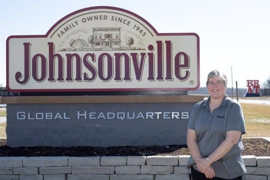 Chris Bodendorfer stands in front of the Johnsonville sign.