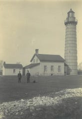 Cana Island Lighthouse as it appeared in 1921, with then-lightkeeper Oscar Knudsen at right.  The 150-year-old light, which is still functional and can be visited by tourists during the summer, hosts an Anniversary celebration Aug. 7.