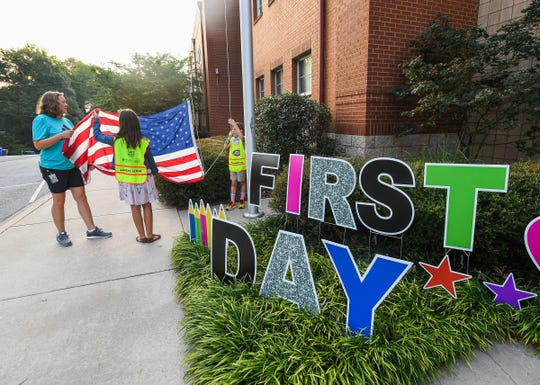 Stone Academy teacher Jill Rohrer helps Jill Rohrer, center, and Aidan Bistyga raise the American flag on the first day of school at Stone Academy in Greenville in 2017.