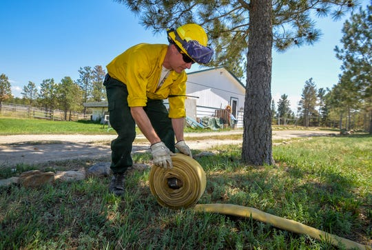 Dan Henderson, of Selkirk Fire Department from Sandpoint, Idaho rolls up a fire hose after performing structure protection around a home on Noble Road, Wednesday afternoon, along the containment line on the North Hills Fire north of Helena.