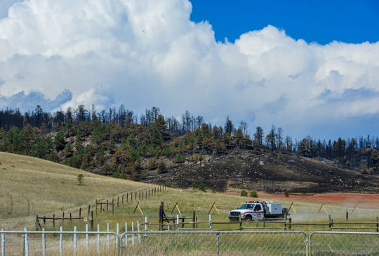 A wildland fire brush truck monitors the fire line on the south end of the North Hills Fire along Noble Lane iWednesday afternoon.