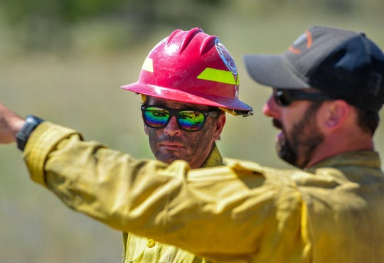 James Douglas, left, of Broadwater County, talks with Jeremiah Miller, a division supervisor on the North Hills Fire, on Wednesday afternoon as crews mopped up hot spots on the southern end of the 4,896-acre fire burning along the Missouri River north of Helena.