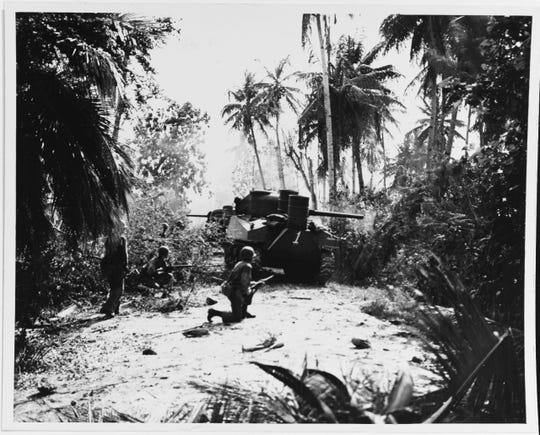 Marine tanks and infantry advance cautiously along a Guam road, July-August 1944.