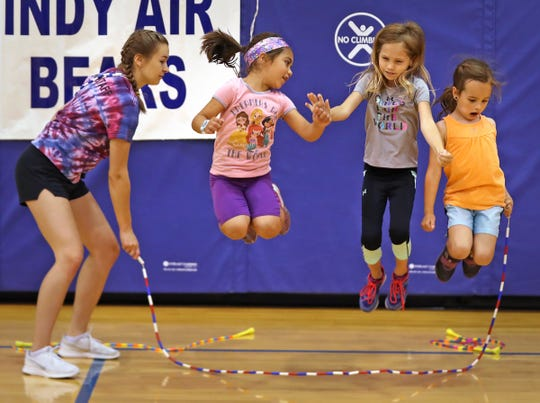 Indy Air Bears jumper Gabby Beck, from left, helps Norah Rairdan, Amelia Wright and Lydia Gorrell as they try out their jumping skills during the Indy Air Bears' annual summer camp at Arlington Elementary School, Wednesday, June 12, 2019. The performance-based team competes locally, nationally and internationally. In July 2019, 12 members of the team traveled to Oslo, Norway, to compete in the World Jump Rope Championship. Their top awards included three world championship titles in Double Dutch events.  Junior competitors also competed in the American Jump Rope Foundation National Championships in Raleigh, North Carolina, in June 2019, winning several gold medals in their events.