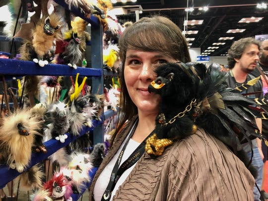 Shari Johnson, who works for The Midsummer Knight's Dream, poses with her griffin puppet.