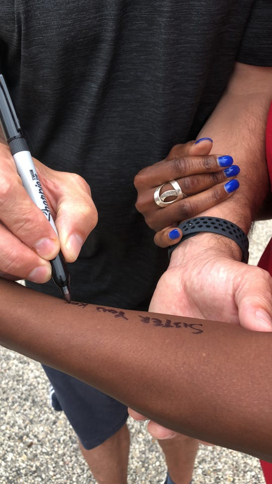 "Dave Matthews writes lyrics to his song, ""Sister,"" on IndyStar columnist Suzette Hackney's arm."