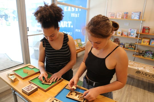 Nina Berry Lofthouse, 14, and Athena Baker-Cogan, 15, both from Ithaca, work on puzzles in the Brain Shoppe.