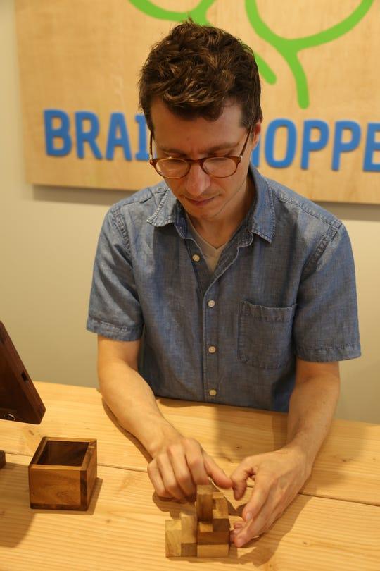 Chris DelCollo works on a soma puzzle.