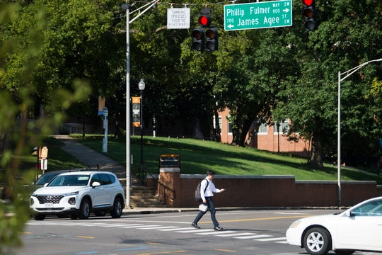 A pedestrian crosses Cumberland Avenue at Phillip Fulmer Way Wednesday evening, July 31, 2019. Crews will replace traffic signals on Cumberland Avenue at the Phillip Fulmer Way, Circle Drive, 13th Street and 11th Street intersections. The new signals will be hung on mast arms rather than wires.