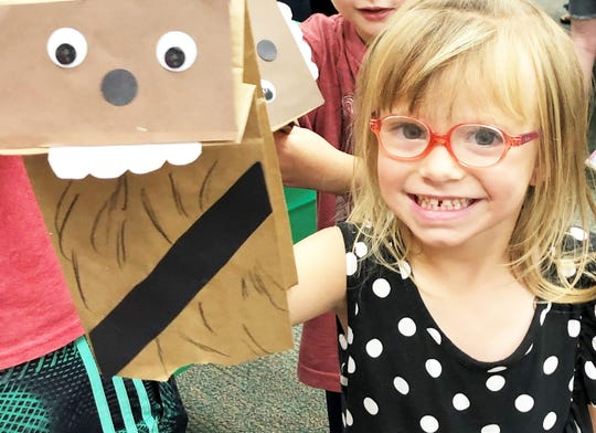 Five-year-old Peyton Lee shows her completed Chewbacca hand puppet at the Halls Branch Library on July 31, 2019.