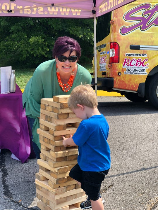 Three-year-old Quinten Starbuck plays Jenga with Kim Hansard at Halls Branch Library's summer block party on July 31, 2019.