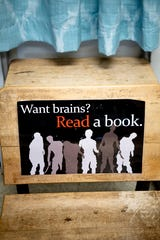 """A sign reading 'Want brains? Read a book."""" sits in an old desk in Robin Bell's classroom  at Gresham Middle School in Knoxville, Tennessee on Thursday, August 1, 2019. Bell is retiring after 30 years of teaching in Knox County Schools."""