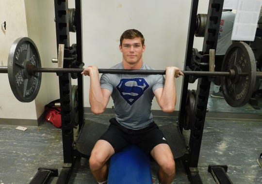 Westminster's Landon Devillier lifts weights during a workout during the summer.