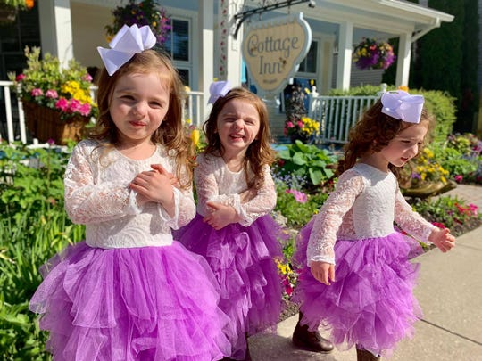 The Buursma triplets play outside The Cottage Inn on Mackinac Island in matching tutus.