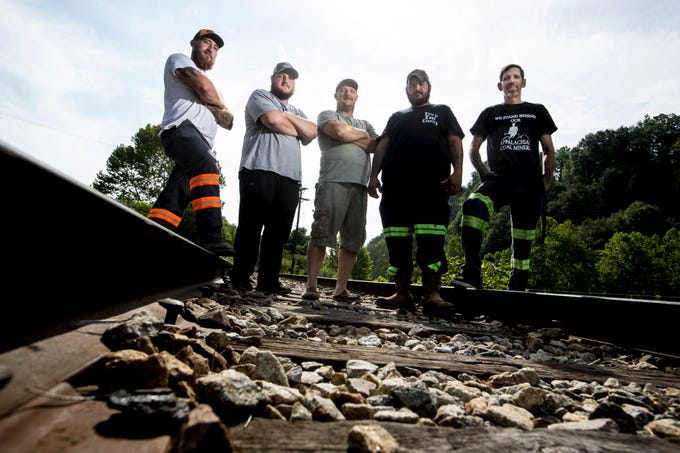 The five miners who stopped a train loaded with coal from the Blackjewell Mining Co. The men are from left to right, Austin Watts, Dalton Lewis, Chris Lewis, Chris Sexton and Jeff Willig. The five men and other coal miner's final checks from the company bounced. A group of the miners have set up a camp and blocked the railroad tracks in Cumberland, in Harlan, County, Ky. Aug. 1, 2019.