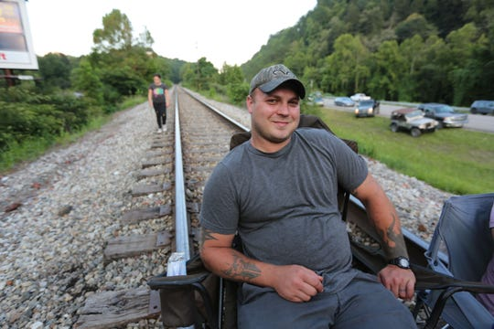 Out-of-work coal miner Stephen Thompson sits in a chair on the tracks. Laid-off Eastern Kentucky coal miners are protesting not getting back pay from Blackjewel by blocking a train from leaving the area with Blackjewel coal.