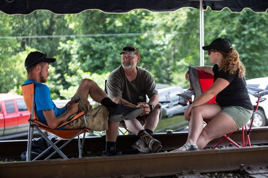 Miners Joe Watts, left, Shawn Tolaver, along with Sarah Bowling occupy a train track in Cumberland. Aug. 1, 2019