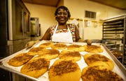 Elizabeth Kizito, owner of Kizito Cookies, pulls a fresh batch of snickerdoodle cookies from the oven during a busy morning of baking. Aug. 1, 2019