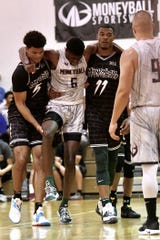 An injured Gabe Brown, center, is carried off the court by MSU teammates Malik Hall, left, and Xavier Tillman during the Moneyball Pro-Am semifinal game on Thursday, Aug. 1, 2019, at Aim High Sports in Dimondale.