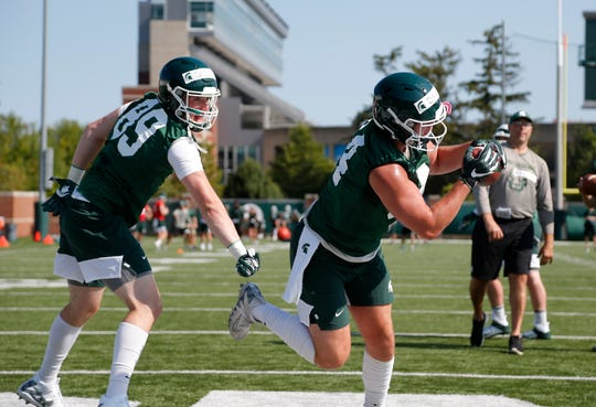 Michigan State's Noah Davis, right, and Matt Dotson run a drill during the first practice of the season, Thursday, Aug. 1, 2019, in East Lansing, Mich.