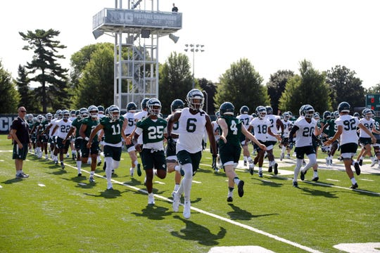 Michigan State players run a drill during their first practice of the season, Thursday, Aug. 1, 2019, in East Lansing, Mich.