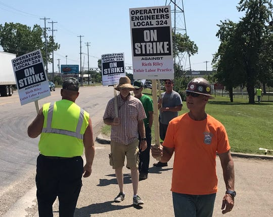 Kevin Zimmerman, right, member of Operating Engineers Local 324, Roger Henfling, middle, worker at Rieth-Riley Construction Company, and others picket outside the Lansing Rieth-Riley facility Thursday. Workers began the strike at 12 a.m. Thursday, protesting labor practices and lack of a contract.