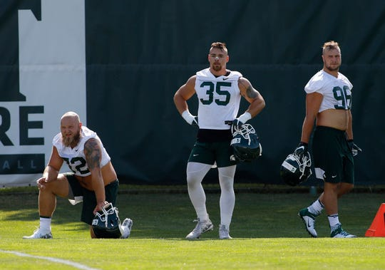 Michigan State's Mike Panasiuk, left, Joe Bachie (35) and Jacub Panasiuk, right, are shown during the first practice of the season, Thursday, Aug. 1, 2019, in East Lansing, Mich.