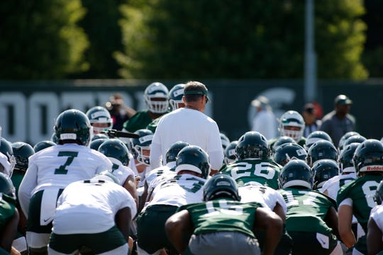 Michigan State players gather around coach Mark Dantonio during the first practice of the season, Aug. 1, 2019, in East Lansing, Mich.