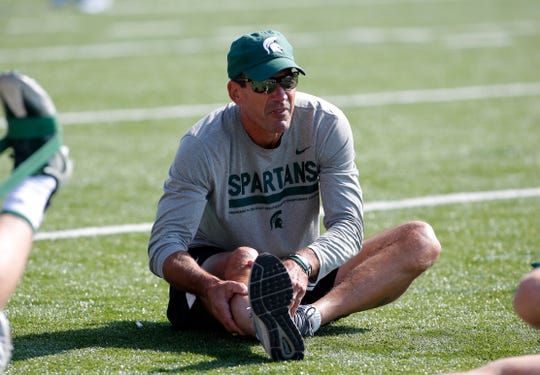 Michigan State assistant coach Dave Warner stretches with players during the first practice of the season, Thursday, Aug. 1, 2019, in East Lansing, Mich.