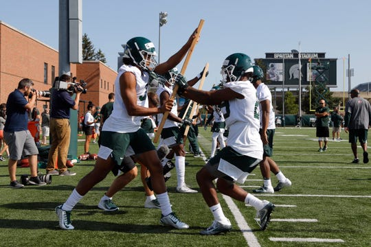 Michigan State players, including Xavier Henderson, left, and Shakur Brown, right, run a drill during the first practice of the season, Thursday, Aug. 1, 2019, in East Lansing, Mich.