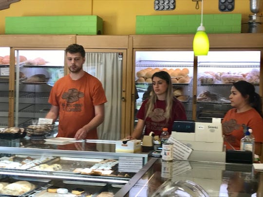 Austin Rehrauer, along with his siblings, works behind the Hartman's Bakery counter