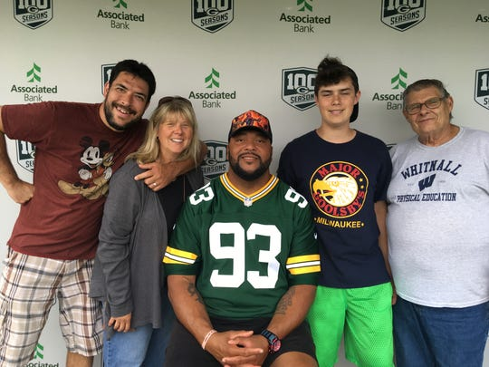 Aaron, Stacy and James Bieniek, and Stacy's father, Tom Kasprzak, pose with Gilbert Brown at Wisconsin State Fair.