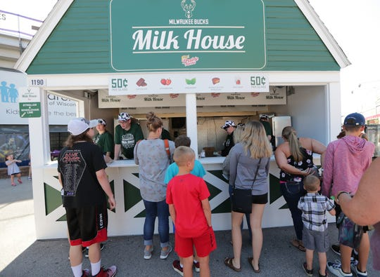 People wait for 50-cent milk Thursday at the Milwaukee Bucks Milk House at the Wisconsin State Fair in West Allis.