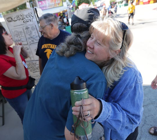 Stacy Bieniek hugs cartoonist Mark Mains on Aug. 1 at the Wisconsin State Fair. She and her family visit Mains every year to get a caricature for their son, James.