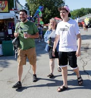 The Bienieks walk around the Wisconsin State Fair in West Allis on Thursday, Aug. 1, 2019. Stacy (center), Aaron (left) and their teenage son James, 15, all from Hales Corners, have gone to the fair every day, every year for at least the past 15 years.