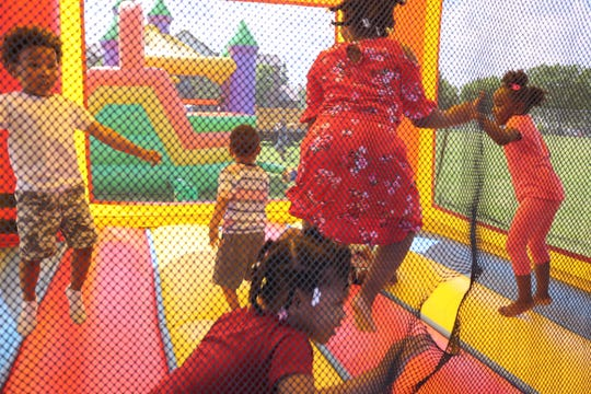 Children jump in one of the bounce houses at Homer Blow's 25th annual birthday party for Milwaukee kids.