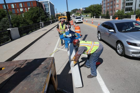 Kurt Rutkowski (rear) and Richard Jones install Jersey walls Thursday on the North Avenue bridge. New concrete barriers installed on two Milwaukee east side bridges will provide more protection for bike lanes.
