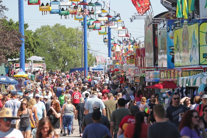 People walk along Grandstand Avenue Thursday at the Wisconsin State Fair in West Allis.