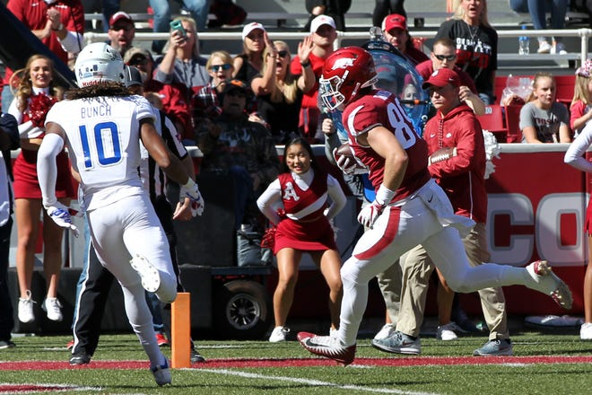 Arkansas tight end Grayson Gunter (89) scores a touchdown in the second quarter as Tulsa Golden Hurricanes safety Manny Bunch (10) looks on at Donald W. Reynolds Razorback Stadium.